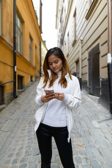 Portrait of young beautiful asian tourist woman traveling around the city of stockholm in sweden