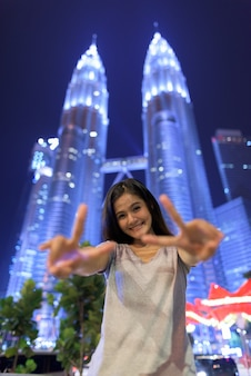 Portrait of young beautiful asian woman against low angle view of the petronas twin towers at night in kuala lumpur, malaysia