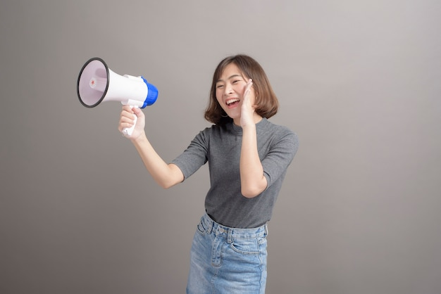 A portrait of young beautiful asian woman holding megaphone on gray