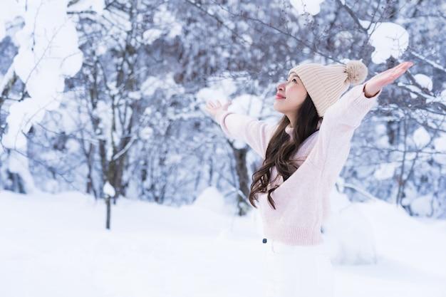 Портрет молодой красивой азиатской улыбкой счастливой женщины путешествуют и наслаждаются со снежным зимним сезоном