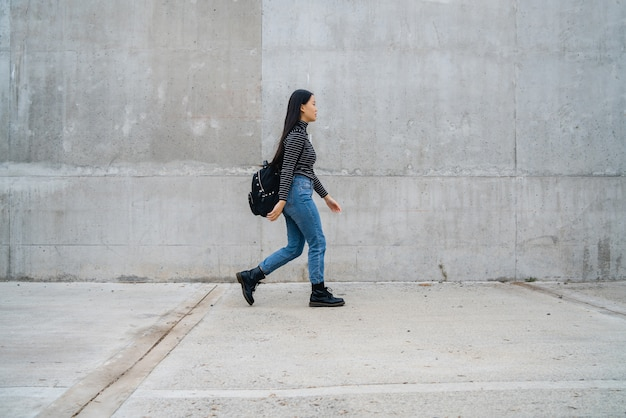 Portrait of young beautiful asian woman walking against grey concrete wall.