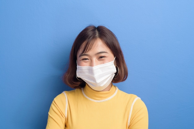 A portrait of young beautiful asian woman wearing a surgical mask