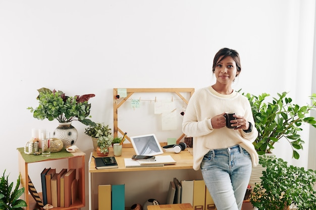 Portrait of young beautiful asian woman with cup of coffee standing at desk in decorated home office and smiling at camera