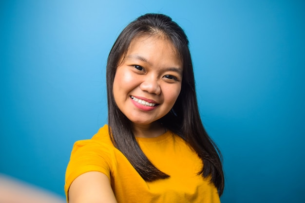 Portrait of young beautiful asian women with blue isolated background taking selfie
