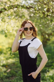 Portrait of young beautiful attractive woman at summer green park
