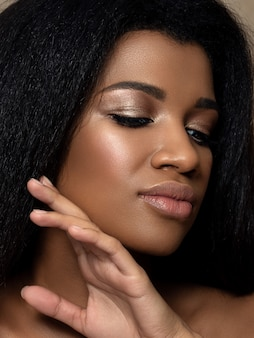 Portrait of young beautiful black woman touching her face