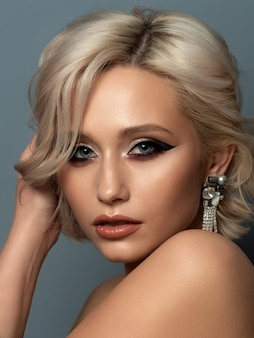 Portrait of young beautiful blond woman with evening make up touching her head. modern fashion eyeliner wing and beautiful earring.