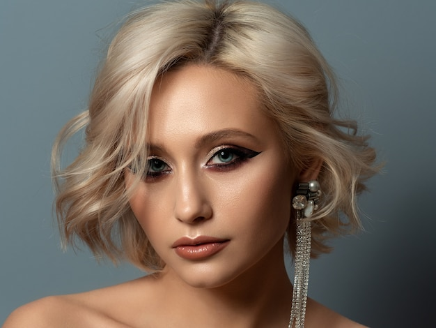 Portrait of young beautiful blond woman with evening make up touching her head