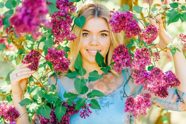 Portrait of young beautiful blonde girl looking through branches with white and purple flowers in summer blooming park.