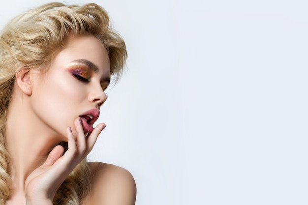 Portrait of young beautiful blonde woman with creative make up and fishtail braids touching her lips