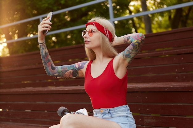 Portrait of young beautiful blonde woman with tattooed arms in a red t-shirt and denim shorts, with a knitted bandana on head, in red glasses, holding smartphone and makes selfie