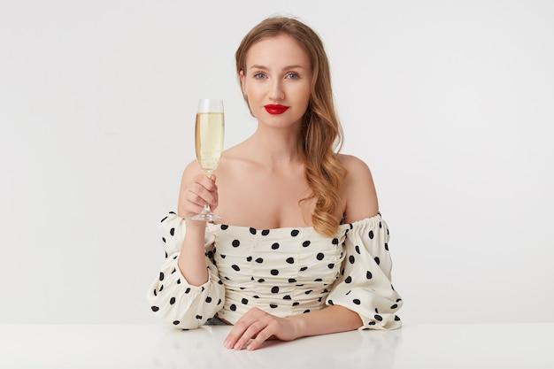 Ritratto di giovane bella donna dagli occhi azzurri con lunghi capelli biondi, con labbra rosse in un abito a pois, posa al tavolo, con in mano un bicchiere di champagne, isolato su sfondo bianco.