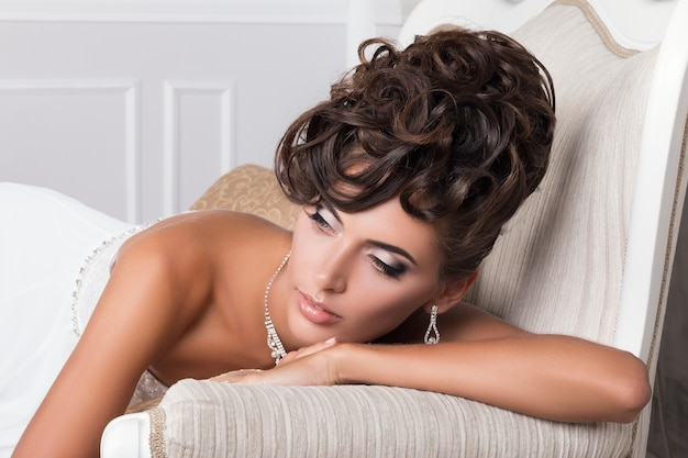 Portrait of young beautiful bride laying on vintage sofa