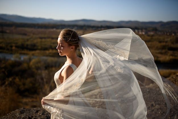 Portrait of a young beautiful bride in the mountains with a veil. the wind develops a veil. wedding photography in the mountains.