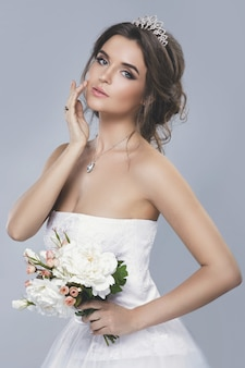 Portrait of young beautiful bride with bouquet of flowers