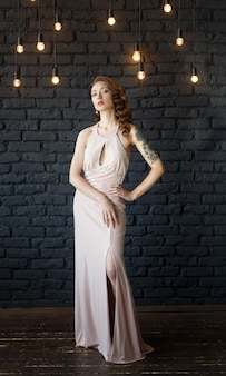 Portrait of a young beautiful brown haired woman in a pink dress