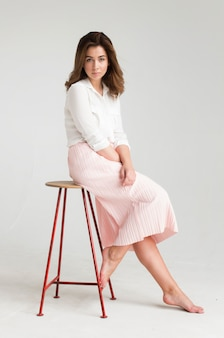 Portrait of a young beautiful brown haired woman in a white blouse and pink skirt sitting on a chair