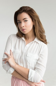 Portrait of a young beautiful brown haired woman in a white blouse and pink skirt