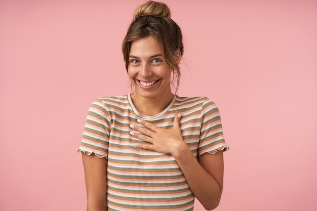Ritratto di giovane bella donna dai capelli castani con trucco naturale guardando allegramente la fotocamera con un ampio sorriso mentre posa su sfondo rosa in abbigliamento casual