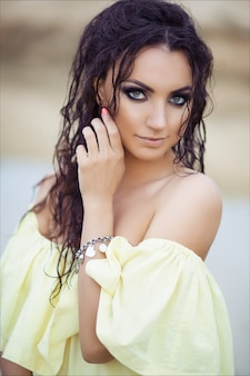 Portrait of young beautiful brunette girl with wet hair in yellow dress.