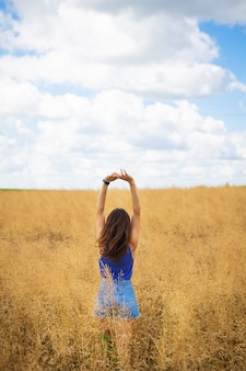 Portrait of a young beautiful brunette woman in a blue t-shirt and denim shorts stands in the middle of the field, exposing her face to the sun