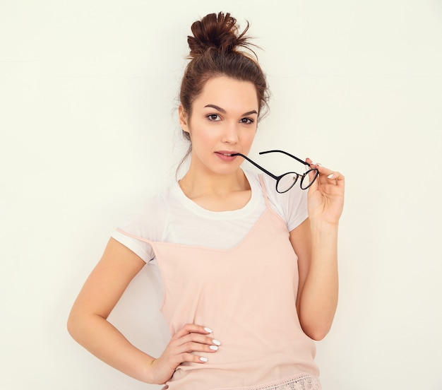 Portrait of young beautiful brunette woman girl model with nude makeup in colorful summer pink hipster clothes posing near wall. biting glasses