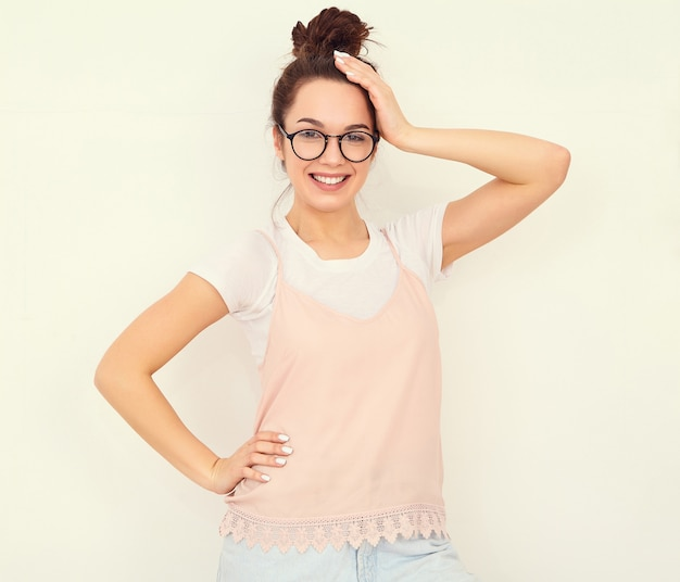 Portrait of young beautiful brunette woman girl model with nude makeup in colorful summer pink hipster clothes posing near wall. looking happily