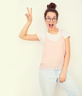 Portrait of young beautiful brunette woman girl model with nude makeup in colorful summer pink hipster clothes posing near wall. showing peace sign