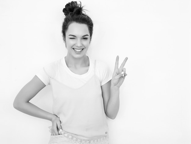 Portrait of young beautiful brunette woman girl model with nude makeup in colorful summer pink hipster clothes posing near wall. winking and showing peace sign