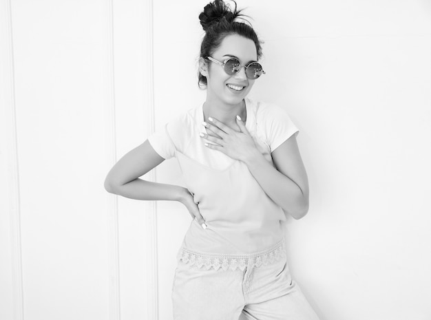 Portrait of young beautiful brunette woman girl model with nude makeup in colorful summer pink hipster clothes in sunglasses posing near wall. looking happily