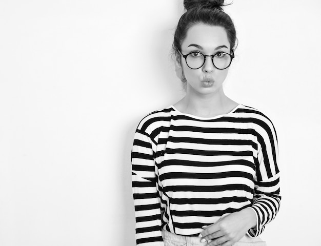 Portrait of young beautiful brunette woman girl model with nude makeup in glasses in summer hipster clothes posing near wall. giving kiss