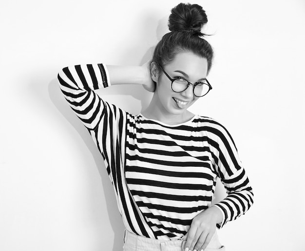 Portrait of young beautiful brunette woman girl model with nude makeup in glasses in summer hipster clothes posing near wall. showing her tongue