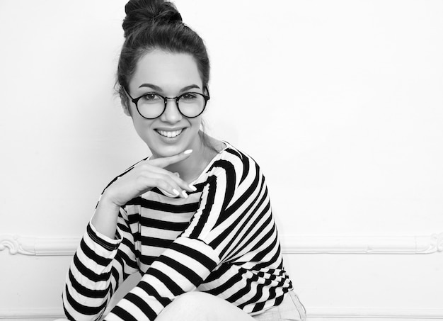 Portrait of young beautiful brunette woman girl model with nude makeup in glasses in summer hipster clothes posing near wall. sitting on the floor