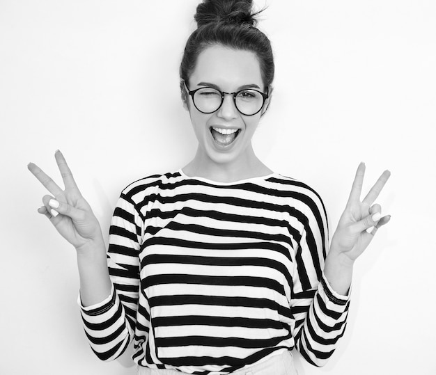 Portrait of young beautiful brunette woman girl model with nude makeup in glasses in summer hipster clothes posing near wall. winking and showing peace sign