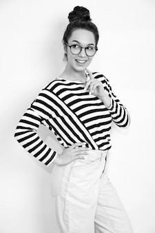 Portrait of young beautiful brunette woman girl model with nude makeup in glasses in summer hipster clothes posing near wall.