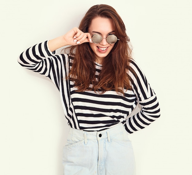Portrait of young beautiful brunette woman girl model with nude makeup in summer hipster clothes and sunglasses posing near wall. showing her tongue