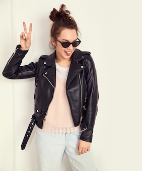 Portrait of young beautiful brunette woman girl model with nude makeup wearing summer hipster biker leather jacket clothes in sunglasses posing near wall. showing her tongue and peace sign