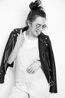 Portrait of young beautiful brunette woman girl model with nude makeup wearing summer hipster biker leather jacket clothes in sunglasses posing near wall. showing her tongue