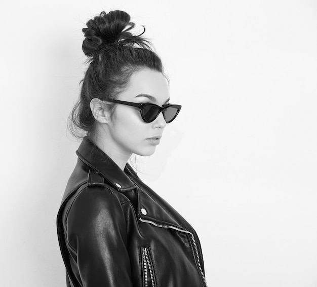 Portrait of young beautiful brunette woman girl model with nude makeup wearing summer hipster biker leather jacket clothes in sunglasses posing near wall.