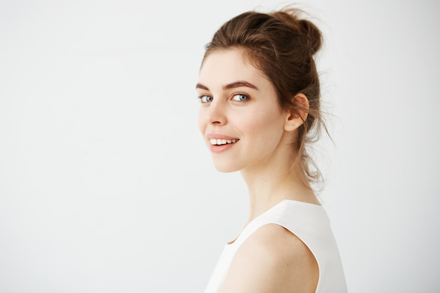 Portrait of young beautiful brunette woman in profile smiling.