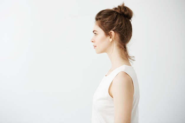 Portrait of young beautiful brunette woman with bun in profile smiling.