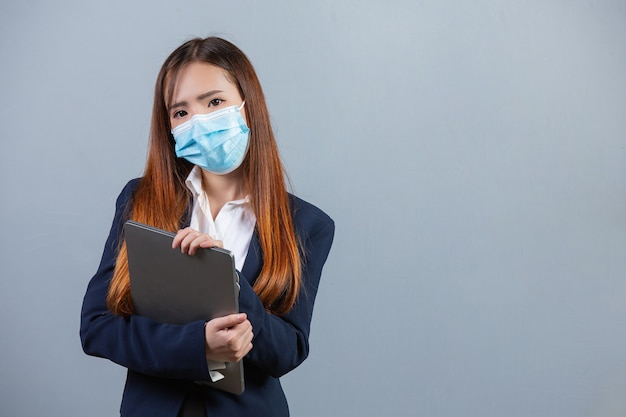 Portrait of young beautiful business woman wearing face mask on gray surface