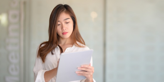 Portrait of young beautiful businesswoman reading company document in modern office