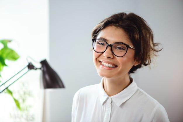 Ritratto di giovane bella donna di affari che sorride nel luogo di lavoro in ufficio.