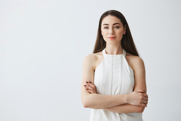 Portrait of young beautiful businesswoman with crossed arms .