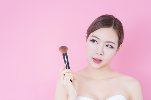 Portrait of young beautiful caucasian asian woman applying cosmetic brush powder. cosmetology, skincare, cleaning face