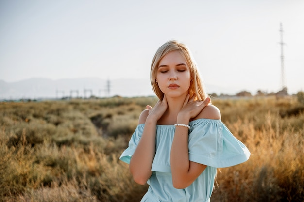 Portrait of young beautiful caucasian blonde girl in light blue dress standing on the field with sun-dried grass during sunset