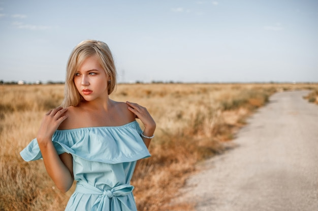 Portrait of a young beautiful caucasian blonde girl in a light blue dress standing on a field with sun-dried grass next to a small country road