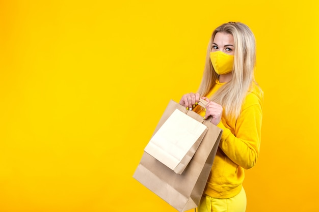 Portrait of young beautiful caucasian blonde woman with paper eco bag in yellow protective mask isolated on yellow background, looking at camera.