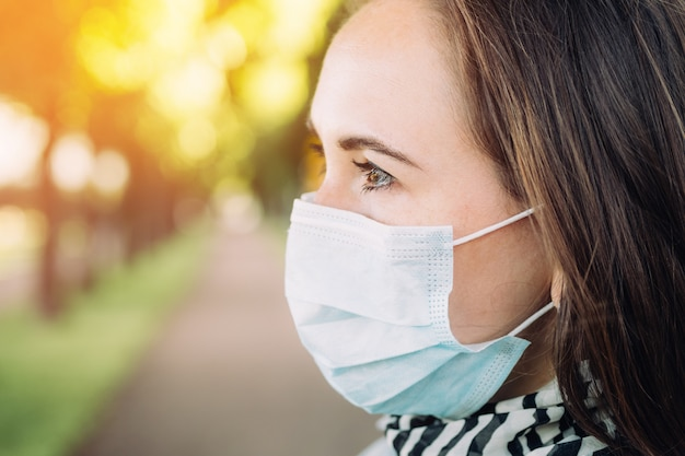 Portrait of a young beautiful caucasian girl in a medical mask on her face in a park. new normality and life during a pandemic.
